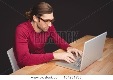 Creative businessman working on laptop at desk in office