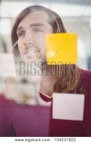Confident businessman standing in front of sticky notes stuck on glass in office