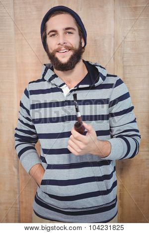 Portrait of happy hipster with hooded shirt holding smoking pipe against wooden wall