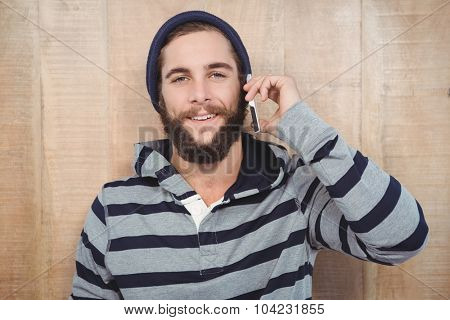 Hipster with hooded shirt using mobile phone against wooden wall