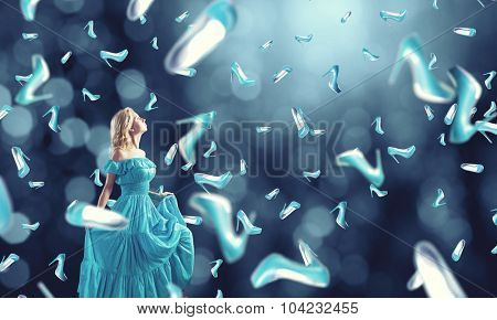 Young cheerful woman in blue dress and many falling shoes