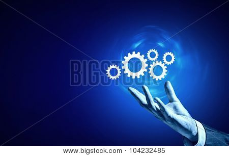 Businessperson hand holding gears and cogwheels in palm