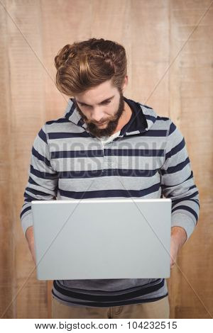 Hipster wearing hooded shirt using laptop against wooden wall