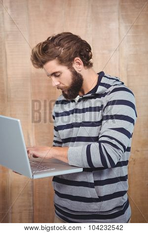 Hipster using laptop while standing against wooden wall