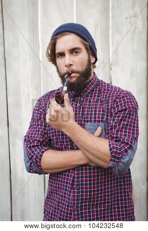 Hipster wearing knitted hat smoking pipe against wooden fence