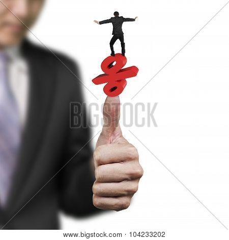 Businessman Balancing Percent Symbol On Another Big Hand Thumb