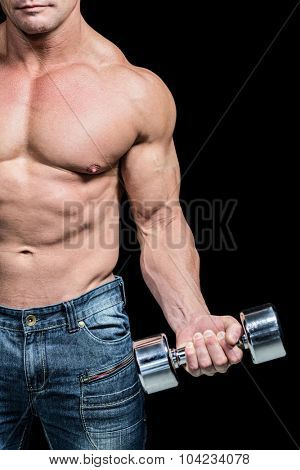 Midsection of bodybuilder exercising lifting dumbbells against black background