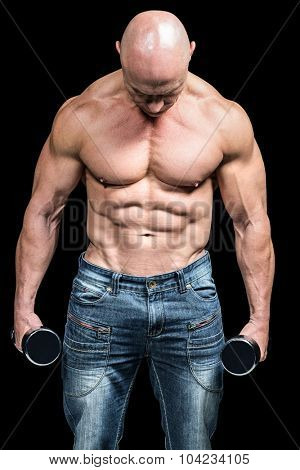Muscular man holding dumbbells against black background