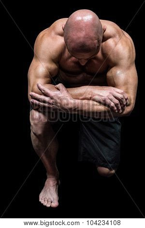 Bodybuilder kneeling down against black background