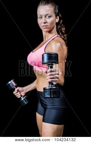 Portrait side view of woman exercising with dumbbells against black background