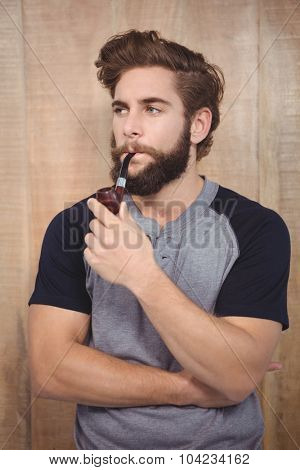 Confident hipster smoking pipe against wooden wall