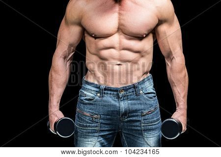 Midsection of bodybuilder with dumbbells against black background
