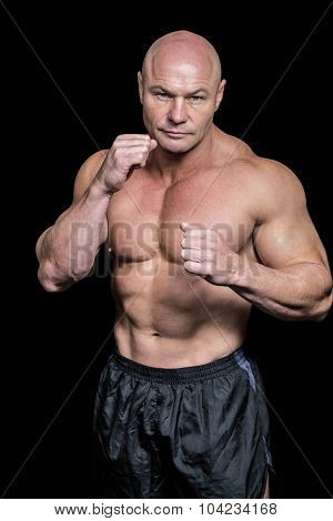 Portrait of bald man with boxing pose against black background