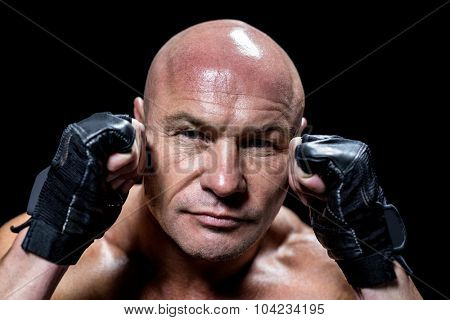 Close-up portrait of confident man with fighting stance against black background