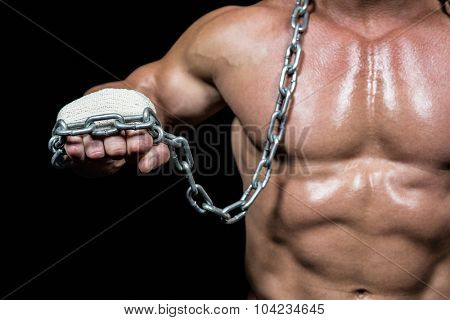 Midsection of man fist with chain against black background