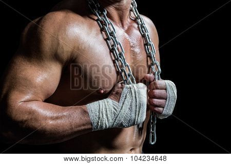 Midsection of bodybuilder holding chain against black background