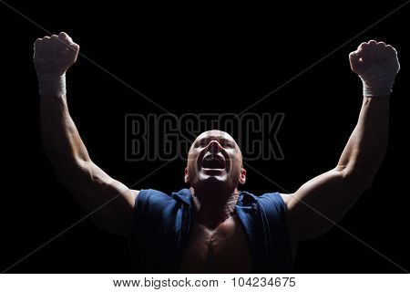 Winner fighter with arms outstretched against black background