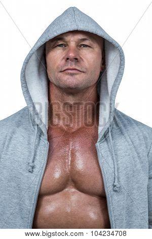 Portrait of confident bodybuilder in hood against white background