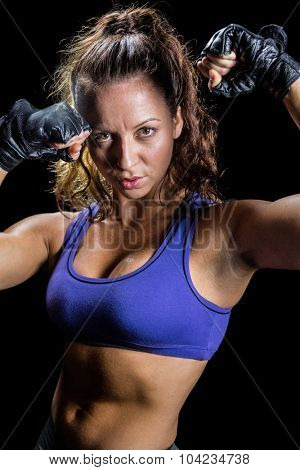 Portrait of bodybuilder with fighting stance against black background
