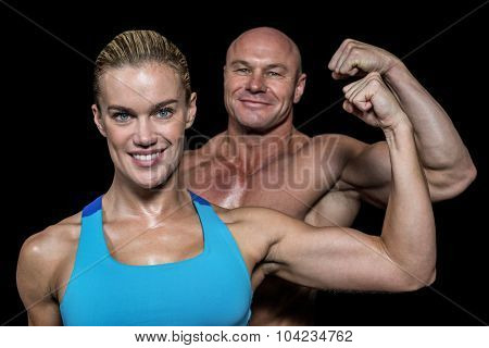 Portrait of confident cheerful man and woman flexing muscles against black background