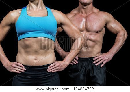 Midsection of muscular woman and man standing with hands on hip against black background