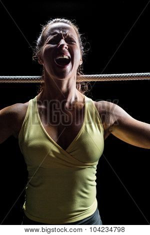Angry woman screaming while holding rope against black background