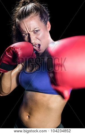 Portrait of aggressive female boxer with fighting stance against black background