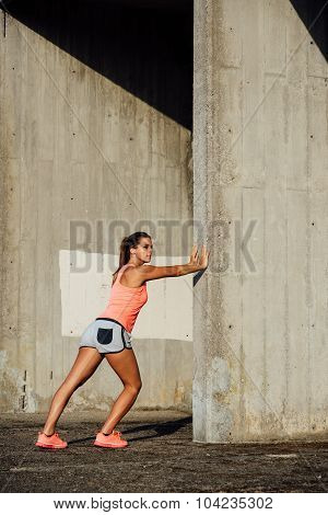 Female Athlete Stretching Legs For Running