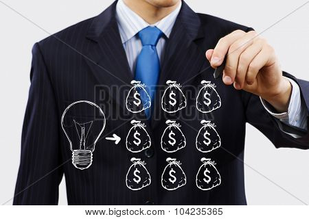 Close up of businessman drawing money making formula