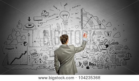 Rear view of businessman drawing business sketch on wall