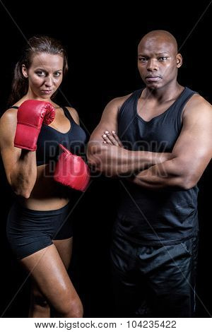 Portrait of male and female athletes standing against black background