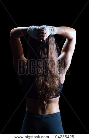 Rear view of female athlete with hands behind head against black background