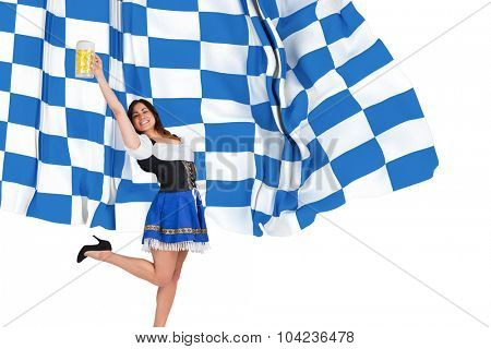 Pretty oktoberfest girl raising beer tankard against blue and white flag