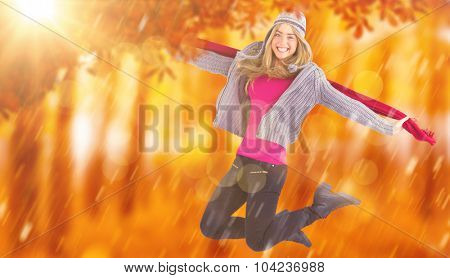 Pretty blonde posing in winter clothes against view of a forest in the mist