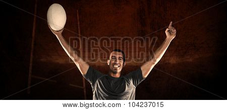 Portrait of rugby player in blue jersey holding ball with arms raised against rugby stadium