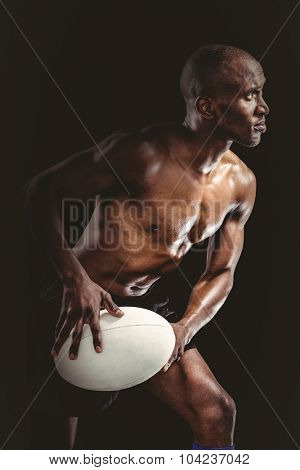 Shirtless sportsman playing while looking away against black background