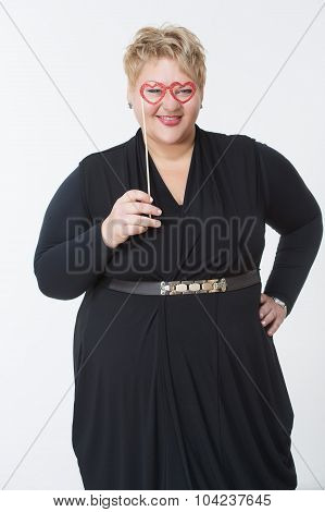 Smiling fat woman holding glasses in the form of hearts