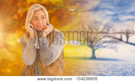 Blonde in winter clothes smiling against autumn turning to winter
