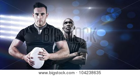 Tough rugby player looking at camera against spotlights