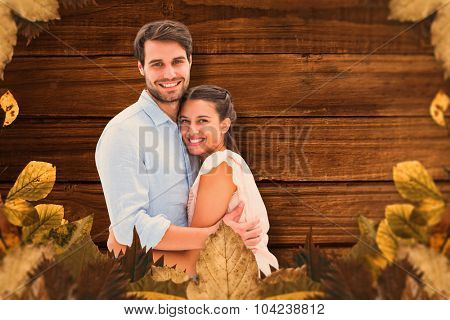 Attractive young couple hugging and smiling at camera against overhead of wooden planks