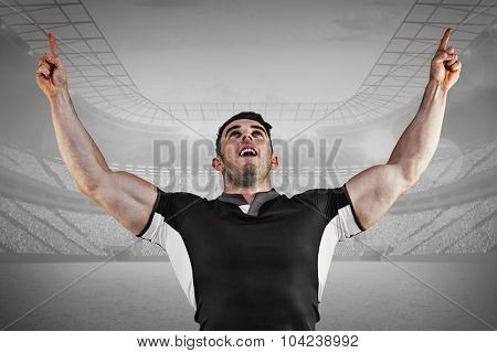Rugby player cheering and pointing against grey vignette