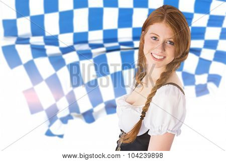 Oktoberfest girl smiling at camera against blue and white flag
