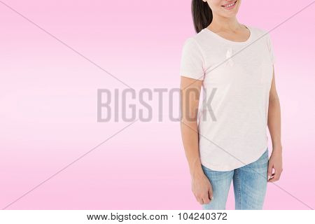 Smiling women in pink for breast cancer awareness against white background with vignette