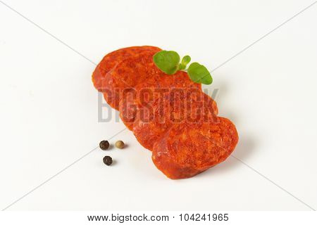 slices of pepperoni sausage in a row on white background