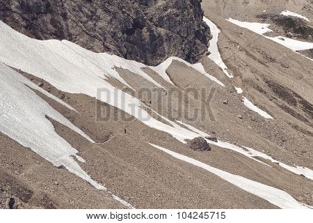 Alpine screed with a permanent snowfield at the foot of a steep rocky peak in the German alps in a close up view of the foot of the peak during a mountain climbing expedition