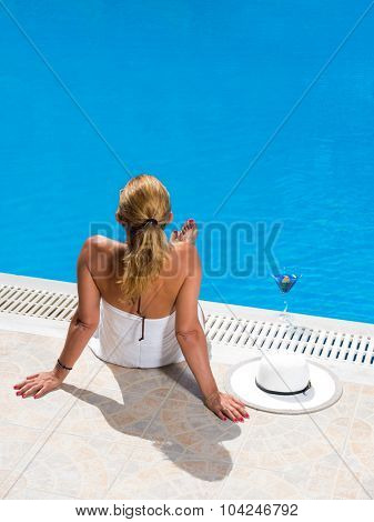 Woman relaxing by the swimming pool in the summertime