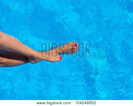 legs of woman lying near the pool . Beautiful female a foot and a heel lifted upwards