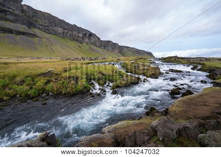 Waterfall cascades flowing into a lake in the southern region of Iceland during summer