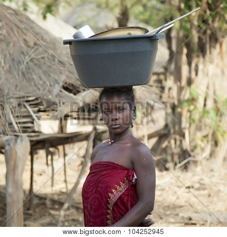 African Woman With A Bucket On Her Head