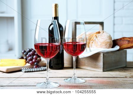 Still life of wine, grape, cheese and bread on light background